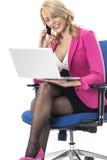 Affärskvinna som använder en bärbar datordator och en mobilmobiltelefon Fotografering för Bildbyråer