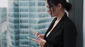 Affärskvinna som använder en mobiltelefon, medan stå på ett högt golv av en skyskrapa nära ett fönster lager videofilmer