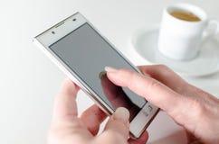 Affärskvinna som använder en smartphone under kaffeavbrott Arkivbild