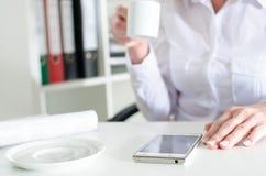 Affärskvinna som använder en smartphone under kaffeavbrott Royaltyfria Foton