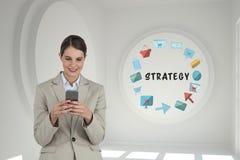 Affärskvinna som använder en telefon i ett rum 3D med ett begreppsmässigt diagram på väggen Royaltyfri Bild