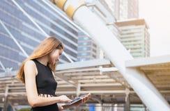 Affärskvinna som använder en utomhus- minnestavladator och arbete arkivfoto