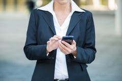 Affärskvinna som använder henne mobil telefon royaltyfri foto
