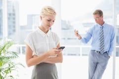 Affärskvinna som använder hennes smartphone med kollegan i bakgrund Royaltyfria Bilder