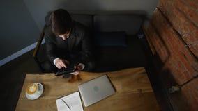 Affärskvinna som använder minnestavladatoren i kafé på den wood tabellen Top beskådar lager videofilmer