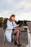 Affärskvinna som använder minnestavlan på lunchavbrott. Arkivfoto