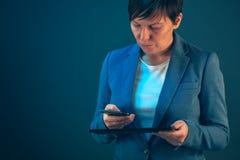 Affärskvinna som använder mobiltelefon- och minnestavladatoren arkivbilder