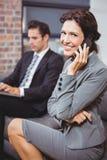 Affärskvinna som använder mobiltelefonen medan kollega i bakgrund Arkivbild