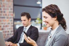 Affärskvinna som använder mobiltelefonen medan kollegaarbete Royaltyfri Fotografi