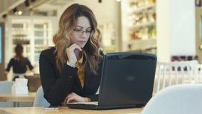 Affärskvinna som arbetar bak bärbara datorn stock video