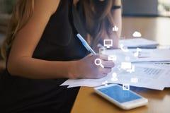 Affärskvinna som arbetar ett kontor med mobila app-symboler Royaltyfria Bilder