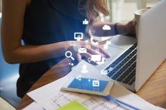 Affärskvinna som arbetar ett kontor med mobila app-symboler Fotografering för Bildbyråer