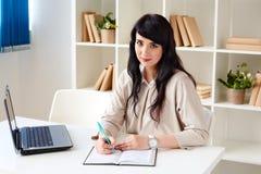 Affärskvinna som arbetar med bärbar datorsammanträde på skrivbordet i kontoret eller klassrumet royaltyfri bild
