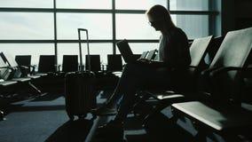 Affärskvinna som arbetar med bärbara datorn i flygplatsterminal Vänta på mitt flyg Kontur mot bakgrunden av a stock video