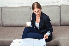 Affärskvinna som arbetar med dokument på soffan arkivbilder