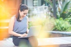 Affärskvinna som arbetar med en bärbar datordator i trädgården royaltyfria bilder