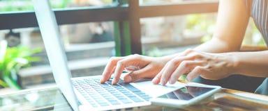 Affärskvinna som arbetar med en bärbar datordator och bruk en mobiltelefon i kontoret royaltyfria bilder