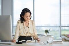 Affärskvinna som arbetar med legitimationshandlingar arkivfoto
