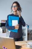 Affärskvinna som arbetar med mobiltelefonen i hennes kontor Arkivbilder