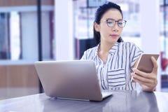 Affärskvinna som arbetar med mobiltelefonen och bärbara datorn royaltyfria bilder