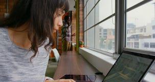 Affärskvinna som arbetar på bärbara datorn i ett modernt kontor 4k arkivfilmer