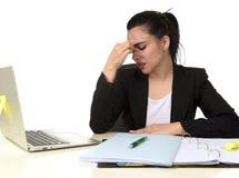 Affärskvinna som arbetar på bärbara datorn på kontoret i spänningen som lider intensiv huvudvärkmigrän Fotografering för Bildbyråer