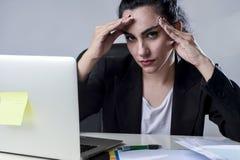 Affärskvinna som arbetar på bärbara datorn på kontoret i spänningen som lider intensiv huvudvärkmigrän Arkivfoton