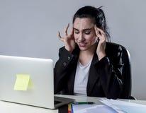 Affärskvinna som arbetar på bärbara datorn på kontoret i spänningen som lider intensiv huvudvärkmigrän Royaltyfri Bild