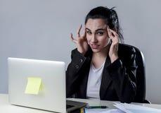 Affärskvinna som arbetar på bärbara datorn på kontoret i spänningen som lider intensiv huvudvärkmigrän Royaltyfri Foto