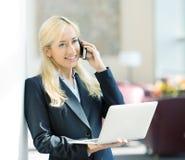 Affärskvinna som arbetar på datoren som kallar på telefonen Arkivbilder