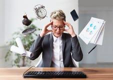 Affärskvinna som arbetar på en bärbar dator som överanstränger, under tryck arkivfoto