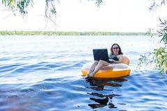 Affärskvinna som arbetar på en bärbar dator i en uppblåsbar cirkel på floden, begreppet av att arbeta på semester royaltyfria bilder