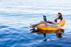 Affärskvinna som arbetar på en bärbar dator i en uppblåsbar cirkel på havet, begreppet av att arbeta på semester royaltyfri fotografi