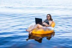 Affärskvinna som arbetar på en bärbar dator i en uppblåsbar cirkel på havet, begreppet av att arbeta på semester arkivbild