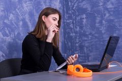 Affärskvinna som arbetar på en bärbar dator och skriver i en anteckningsbok, avlägset arbete royaltyfri foto