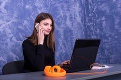 Affärskvinna som arbetar på en bärbar dator och talar på telefonen, avlägset arbete arkivfoton