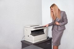 Affärskvinna som arbetar på en kopieringsmaskin på kontoret Royaltyfri Fotografi