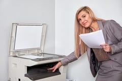 Affärskvinna som arbetar på en kopieringsmaskin på kontoret Arkivfoto