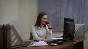 Affärskvinna som arbetar på hennes dator och talar på telefonen lager videofilmer