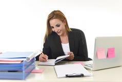 Affärskvinna som arbetar på skrivbordet för kontor för bärbar datordator som tar anmärkningar som skriver på anteckningsboken Royaltyfri Fotografi