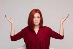 Affärskvinna som bär i rött ha passiv sinnesrörelse och se frustrerat royaltyfria foton