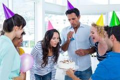 Affärskvinna som blåser stearinljus på hennes födelsedagkaka arkivfoton