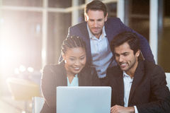 Affärskvinna som diskuterar med kollegor över bärbara datorn royaltyfria foton