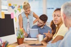 Affärskvinna som diskuterar med manliga kollegor som använder den digitala minnestavlan royaltyfri bild