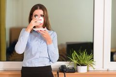 Affärskvinna som dricker ett kaffe för arbete i kontoret Royaltyfria Bilder