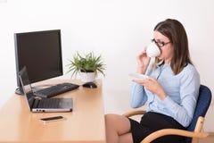 Affärskvinna som dricker ett morgonkaffe i kontoret Royaltyfri Fotografi