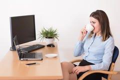 Affärskvinna som dricker ett morgonkaffe i kontoret Arkivfoto