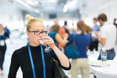 Affärskvinna som dricker exponeringsglas av vatten under avbrott på affärskonferensen Arkivfoton