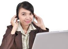 Affärskvinna som fungerar genom att använda hörlurar med mikrofon och bärbar dator Arkivbild