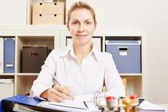 Affärskvinna som fungerar på skrivbordet Arkivbild